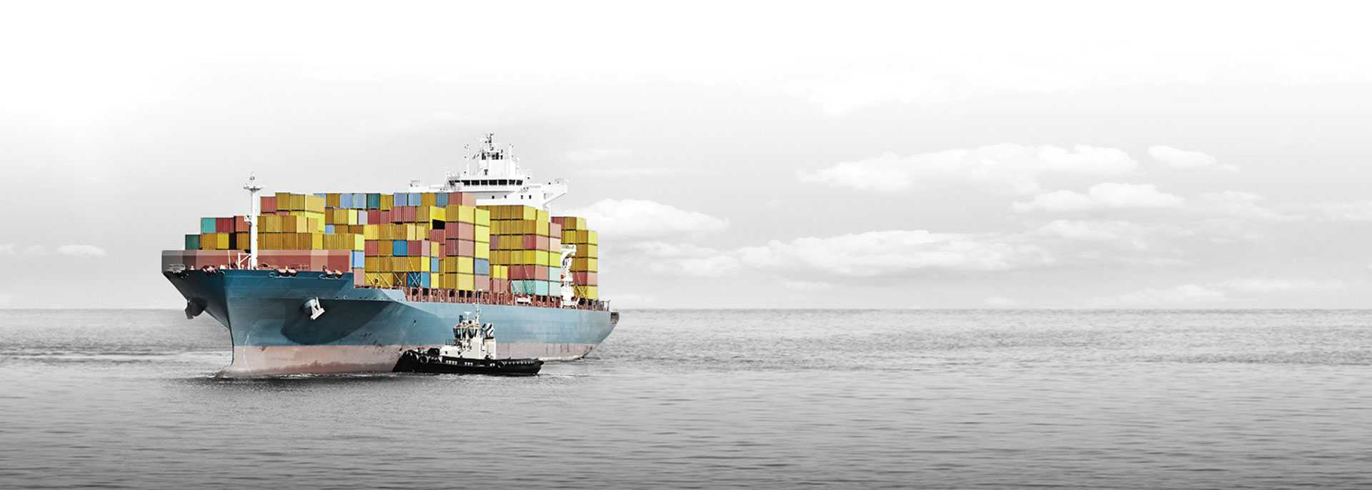 Large shipping boat on the open ocean, the boat and shipping containers are in color and the rest in black and white