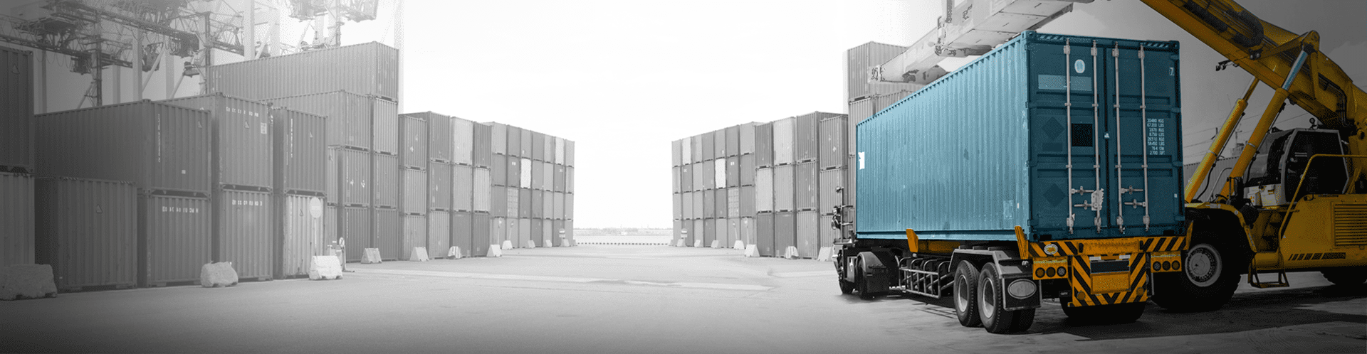 A shipyard full of shipping containers, the front shipping container and forklift are in color, the rest in black and white